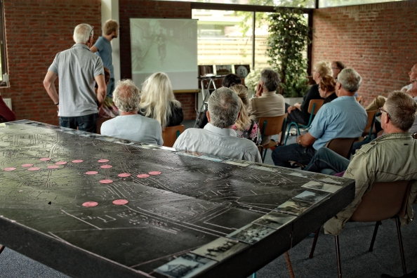 De inwoners van Hallum kijken naar een presentatie door Landschaphistoricus Jeroen Wiersma. voor de grote tafel met een grote kaart van historisch Hallum